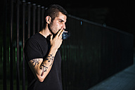 Young man smoking on a street at night at night - JASF000069