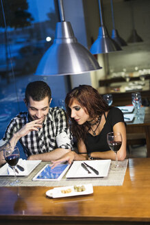 Young couple with digital tablet in a restaurant at night - JASF000072