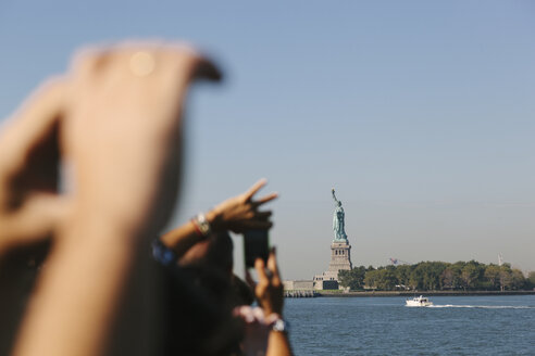 USA, New York City, tourists taking picture of Statue of Liberty - GIO000106