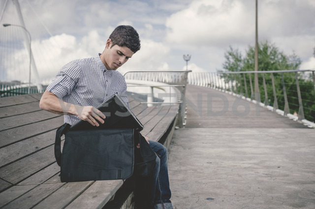 Spain, Ferrol, young man taking his laptop out of a bag - RAEF000484