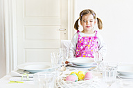 Portrai of smiling little with closed eyes girl standing behind laid table - LVF003777