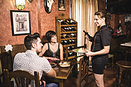 Waitress serving plate with salad and red wine to couple in restaurant - JASF000088