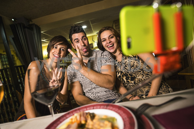 Three playful friends in a restaurant taking a selfie - JASF000092