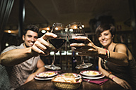 Happy couple in a bar toasting red wine glasses - JASF000095