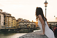 Italy, Florence, woman watching sunset behind Ponte Vecchio - GEMF000353