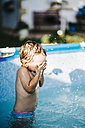 Liittle boy standing in a paddling pool covering eyes with his hands - JRFF000046