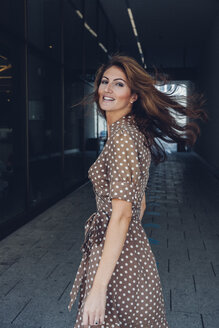 Portrait of smiling brunette woman at underpass - CHAF001397