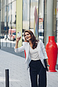 Smiling businesswoman on pavement hailing a taxi - CHAF001407