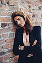 Portrait of smiling businesswoman leaning against brick wall - CHAF001423