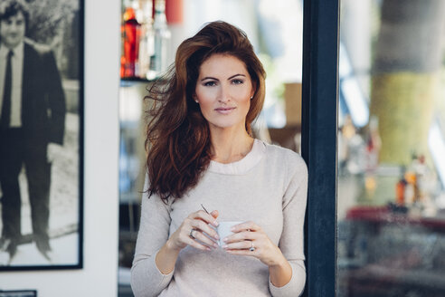 Smiling woman outdoors holding cup of coffee - CHA001431
