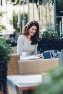 Smiling woman looking in shopping bag at outdoor cafe - CHAF001434