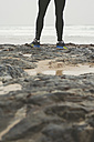Legs of a jogger on the rocks of a beach - RAEF000472