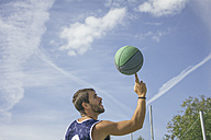 Man spinning a basketball on his finger - ABZF000109