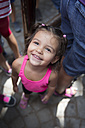 Portrait of smiling little girl standing between adults looking up - ERL000022