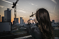 Germany, Frankfurt, back view of young woman taking a picture with smartphone at twilight - RIBF000251