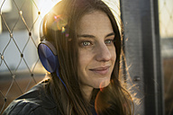 Germany, Frankfurt, portrait of smiling woman hearing music with headphones at backlight - RIBF000256