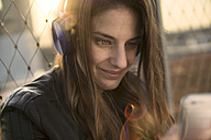 Germany, Frankfurt, portrait of smiling woman hearing music with headphones looking at smartphone - RIBF000258
