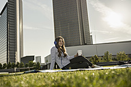 Germany, Frankfurt, young woman sitting on blanket on a meadow hearing music with headphones - RIBF000252
