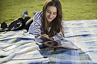 Young woman lying on blanket on a meadow reading magazine - RIBF000310