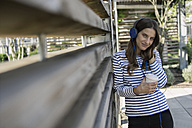 Portrait of smiling woman with coffee to go hearing music with headphones - RIBF000270