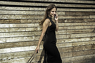 Portrait of smiling businesswoman telephoning with smartphone in front of wooden wall - RIBF000303
