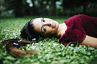 Portrait young woman lying on a meadow - JRFF000065