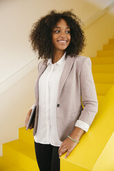 Portrait of smiling teenage girl standing on yellow stairs - MFF002100