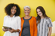 Group picture of three smiling women standing in front of a yellow wall - MFF002112