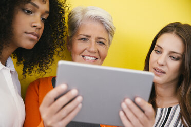 Three women looking at digital tablet in front of a yellow wall - MFF002115