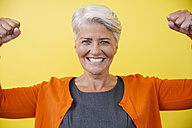 Portrait of mature woman standing like superwoman in front of a yellow wall - MFF002118