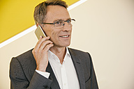 Portrait of mature man wearing glasses telephoning with smartphone - MFF002132