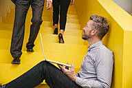 Mature man with laptop sitting on yellow stairs looking up to a colleague - MFF002124