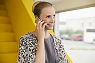 Portrait of smiling young woman telephoning with smartphone in front of yellow stairs - MFF002129