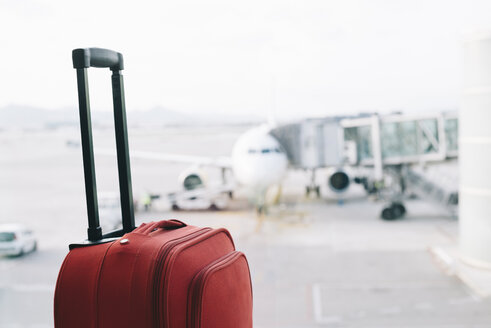 Red suitcase at airport, airplane in background - GEMF000357