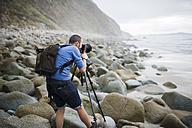 Spain, Valdovino, photographer on the beach with tripod and camera - RAEF000473