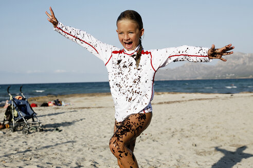 Spain, Mallorca, laughing little girl covered with seaweed on the beach - TMF000035