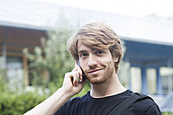 Portrait of smiling young man telephoning with smartphone - SGF001872
