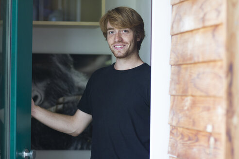 Portrait of smiling young man opening entry door - SGF001877