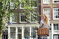 Netherlands, Amsterdam, woman with bicycle and cell phone in the city - FMKF002096
