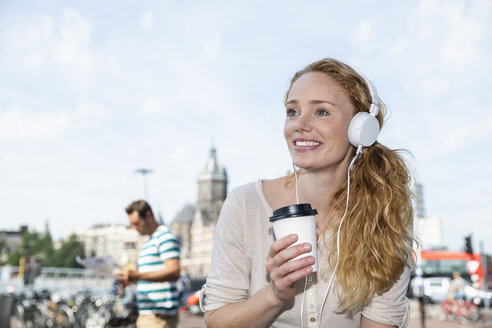 Netherlands, Amsterdam, smiling woman with headphones and coffee to go in the city - FMKF002109