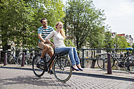 Netherlands, Amsterdam, happy couple riding bicycle in the city - FMKF002214