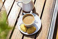 Cup of coffee with cookies on table outdoors - FMKF002117