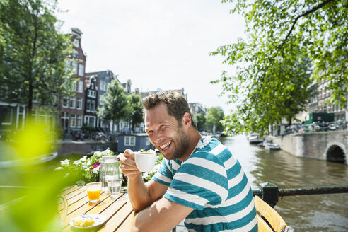 Netherlands, Amsterdam, happy man drinking cup of coffee at town canal - FMKF002120