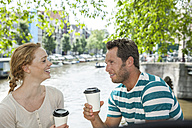 Netherlands, Amsterdam, couple with coffee to go at town canal - FMKF002131