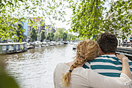 Netherlands, Amsterdam, couple embracing at town canal - FMKF002136