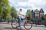 Netherlands, Amsterdam, woman riding bicycle  in the city - FMKF002145