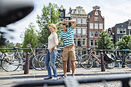 Netherlands, Amsterdam, happy couple in the city - FMKF002151