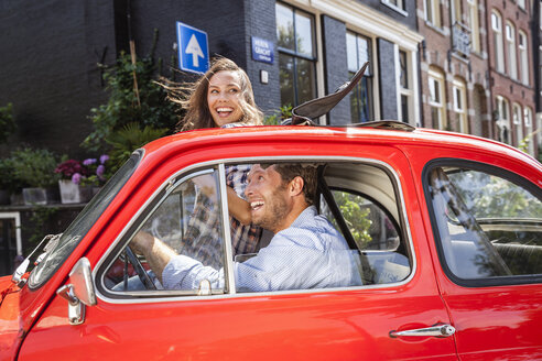 Netherlands, Amsterdam, happy couple with small car in the city - FMKF002157