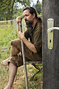 Man sitting with hiking pole at wooden hut - MIDF000606