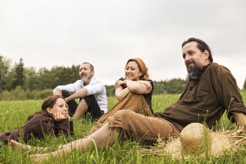 Businessman having a break on the countryside with three villagers - MIDF000619